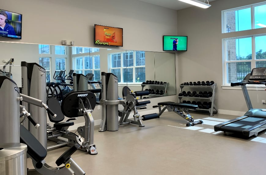 workout room with treadmills, weights, and other exercise machines.